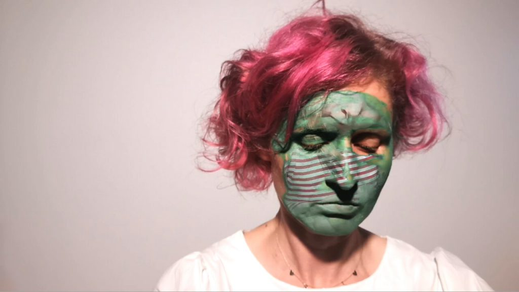 EL Putnam has pink hair and is wearing white. She is looking downwards with green paint on her face and overlay of child.