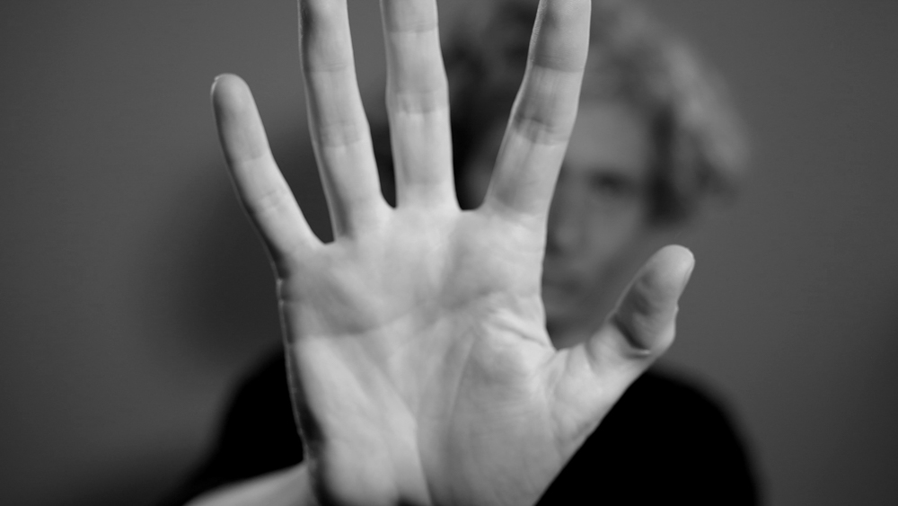 Black and white image with hand filling the screen, face is visible out of focus and in background