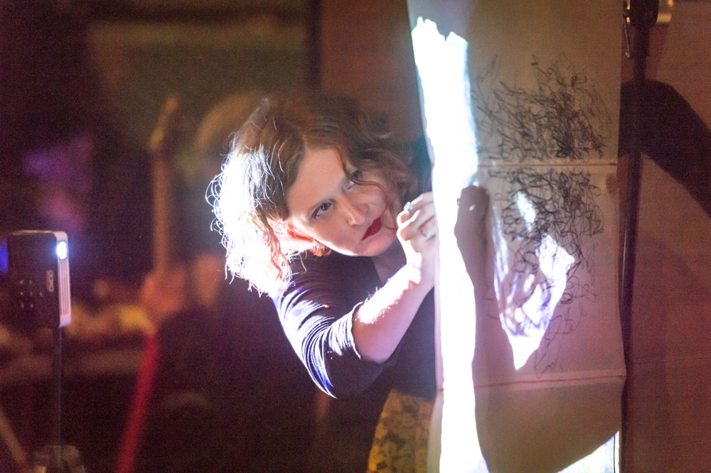 EL Putnam writes on a hanging piece of semi-transparent paper with light shining through it